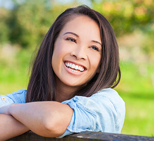 Young lady leaning on wooden rail smiling