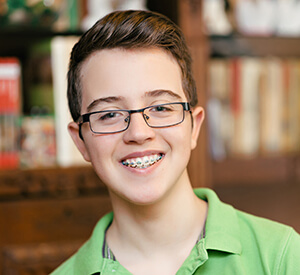 Young boy with glasses and braces smiling