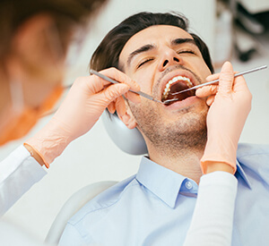 Man receiving dental examination from dentist
