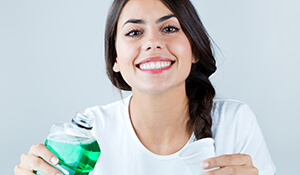 Lady smiling and holding oral rinse