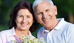 Senior man and woman holding flowers outdoors