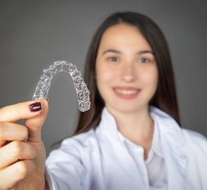 Richardson Invisalign woman placing her invisalign braces