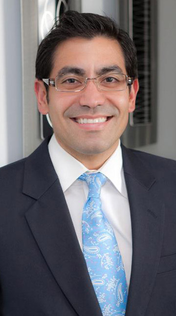 Dr. Javier Ortiz wearing suit smiling