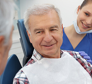elderly man on dental chair smiling