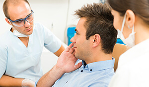 Dentist examing patient's cheek pain