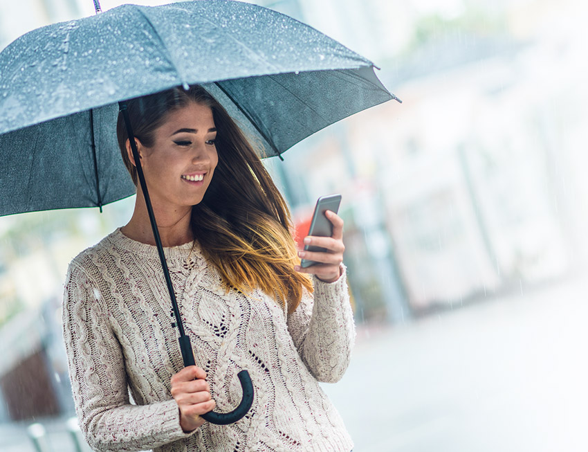 Lady holding umbrella and phone in rain smiling
