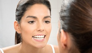 Woman examining her straight teeth in mirror