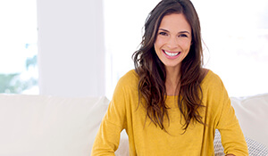 Woman in yellow smiling brightly