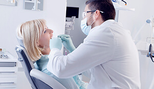 dentist examining female patient's mouth
