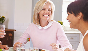 Two ladies laughing at dinner table