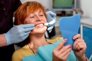 An older woman viewing her new dental implants.